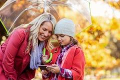 Mutter und Tochter, die im Mobiltelefon Park betrachten Lizenzfreies Stockfoto