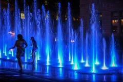 Mutter und Tochter, die im Wasserbrunnen nachts in Quebec spielen lizenzfreies stockbild