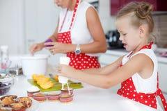 Mutter und Tochter, die kleine Kuchen in eine große helle Küche kochen Lizenzfreie Stockfotografie