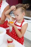 Mutter und Tochter, die kleine Kuchen in eine große helle Küche kochen Stockbilder