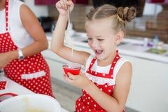 Mutter und Tochter, die kleine Kuchen in eine große helle Küche kochen Lizenzfreie Stockbilder