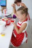 Mutter und Tochter, die kleine Kuchen in eine große helle Küche kochen Stockfotos
