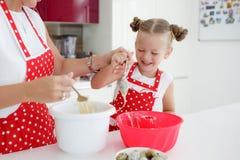 Mutter und Tochter, die kleine Kuchen in eine große helle Küche kochen Stockfotografie
