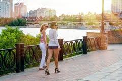 Mutter und Tochter, die, lächelnd spricht und gehen durch den Stadtpark stockfotografie