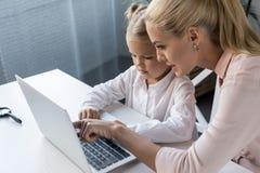 Mutter und Tochter, die Laptop verwendet Stockfotografie