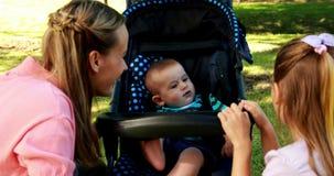 Mutter und Tochter, die mit Baby in einem Pram im Park spielen stock video footage