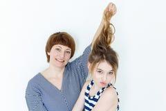 Mutter und Tochter, die mit dem blonden langen Haar spielen Stockfoto