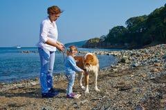 Mutter und Tochter, die mit einem Hund spielen Lizenzfreies Stockbild