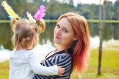 Mutter und Tochter, die mit Federn im Park spielen Stockfoto