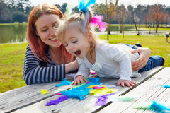 Mutter und Tochter, die mit Federn im Park spielen Stockbilder