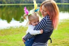 Mutter und Tochter, die mit Federn im Park spielen Lizenzfreies Stockbild