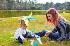 Mutter und Tochter, die mit Federn im Park spielen Lizenzfreie Stockbilder