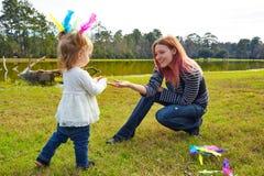 Mutter und Tochter, die mit Federn im Park spielen Stockfotos