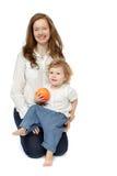 Mutter und Tochter, die mit Frucht sitzen Stockbild