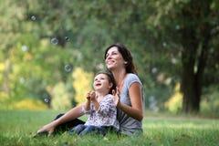 Mutter und Tochter, die mit Luftblase spielen Stockfoto