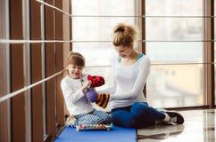 Mutter und Tochter, die mit Spielwaren in der Turnhalle spielen Lizenzfreie Stockfotos