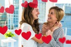 Mutter und Tochter, die mit Zeichnungen des Herzens lachen Stockbild