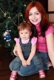 Mutter und Tochter, die nahe Weihnachtsbaum sitzen Stockbild