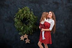 Mutter und Tochter, die nahe Weihnachtskranz spielen stockbilder