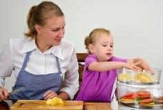 Mutter und Tochter, die Nahrung zubereiten Lizenzfreie Stockfotografie