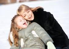 Mutter und Tochter, die schönen Wintertag genießen Stockfotografie