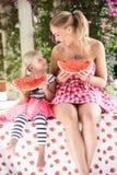 Mutter und Tochter, die Scheiben der Wassermelone genießen Stockfotos