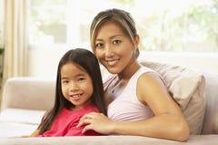 Mutter und Tochter, die sich zu Hause auf Sofa entspannen Stockbild