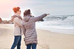 Mutter und Tochter, die Sonnenuntergang auf dem Strand genießen stockfotografie