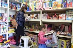 Mutter und Tochter, die Spielwaren in einer Ludothek vorwählen lizenzfreies stockbild