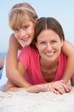 Mutter und Tochter, die am Strand-Feiertag sich entspannen lizenzfreies stockbild