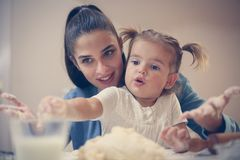 Mutter und Tochter, die Teig für Plätzchen und das Spielen machen lizenzfreie stockfotos