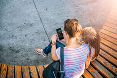 Mutter und Tochter, die Telefon im Park verwendet lizenzfreie stockfotografie