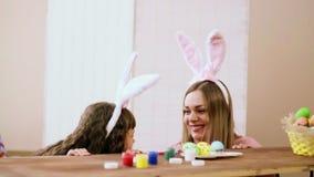 Mutter und Tochter, die am Tisch betrachtet einander und das Trauen sitzt stock footage