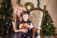 Mutter und Tochter, die unter Weihnachtsbaum sitzen Lizenzfreie Stockbilder