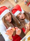 Mutter und Tochter, die Weihnachtsbonbons tun Stockbild