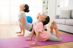 Mutter und Tochter, die Yogaübungen tun Lizenzfreie Stockfotografie