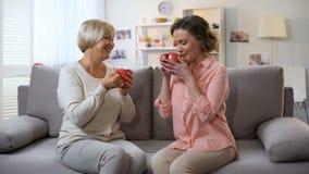Mutter und Tochter, die zu Hause, entspannend auf Sofa mit Tasse Kaffees, Vertrauen spricht stock video footage