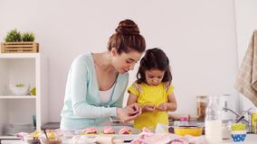 Mutter und Tochter, die zu Hause kleine Kuchen kochen stock footage