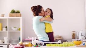 Mutter und Tochter, die zu Hause kochen und umarmen stock footage