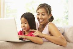 Mutter und Tochter, die zu Hause Laptop verwendet Stockfotografie