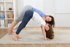 Mutter und Tochter, die zu Hause Yoga durchführen Stockbild