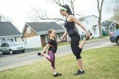 Mutter und Tochter, die zusammen Übungen tun Lizenzfreie Stockbilder