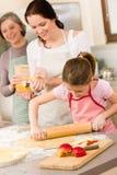 Mutter und Tochter, die zusammen Apfelkuchen bilden Stockbilder