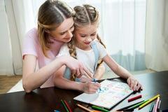 Mutter und Tochter, die zusammen bunte Buchstaben zeichnen Stockbild