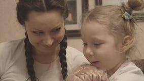 Mutter und Tochter, die zusammen ein Buch über Dinosaurier lesen stock video footage