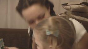Mutter und Tochter, die zusammen ein Buch über Dinosaurier lesen stock footage