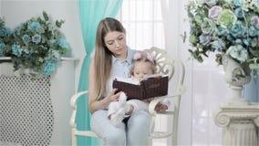 Mutter und Tochter, die zusammen ein Buch lesen stock footage