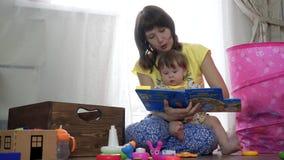 Mutter und Tochter, die zusammen ein Buch lesen stock video