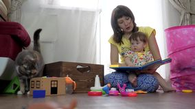 Mutter und Tochter, die zusammen ein Buch lesen stock video footage