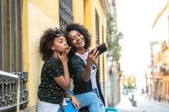 Mutter und Tochter, die zusammen ein selfie nehmen lizenzfreie stockbilder
